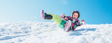 Little Happy Girl Slides Down From The Snow Slope With Blue Sky Background