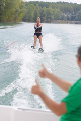 Fototapeta young woman learning to water skiing on a lake