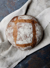 An Artisan Loaf Of Bread Cools On A Cloth.