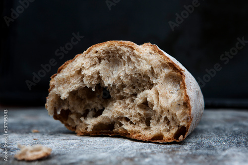Foto op Plexiglas Eten A multigrain loaf of bread is broken open on a rustic surface.