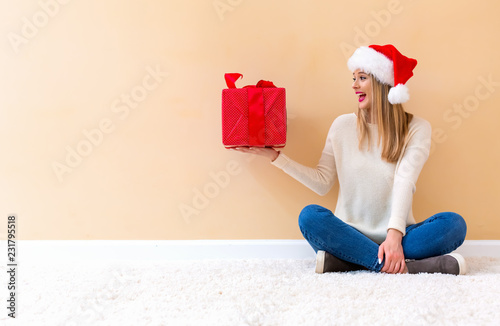 Spoed Foto op Canvas Wanddecoratie met eigen foto Young woman with santa hat holding a gift box on a white carpet