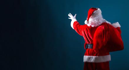 Santa holding a red sack on a dark blue background