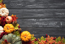 Top View Of  Autumn Maple Leaves With Pumpkin And Red Berries On Old Wooden Background. Thanksgiving Day Concept.