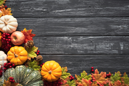 Obraz Top view of  Autumn maple leaves with Pumpkin and red berries on old wooden background. Thanksgiving day concept. - fototapety do salonu