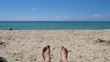 First person perspective of being barefoot and lying down on a sunny sandy beach