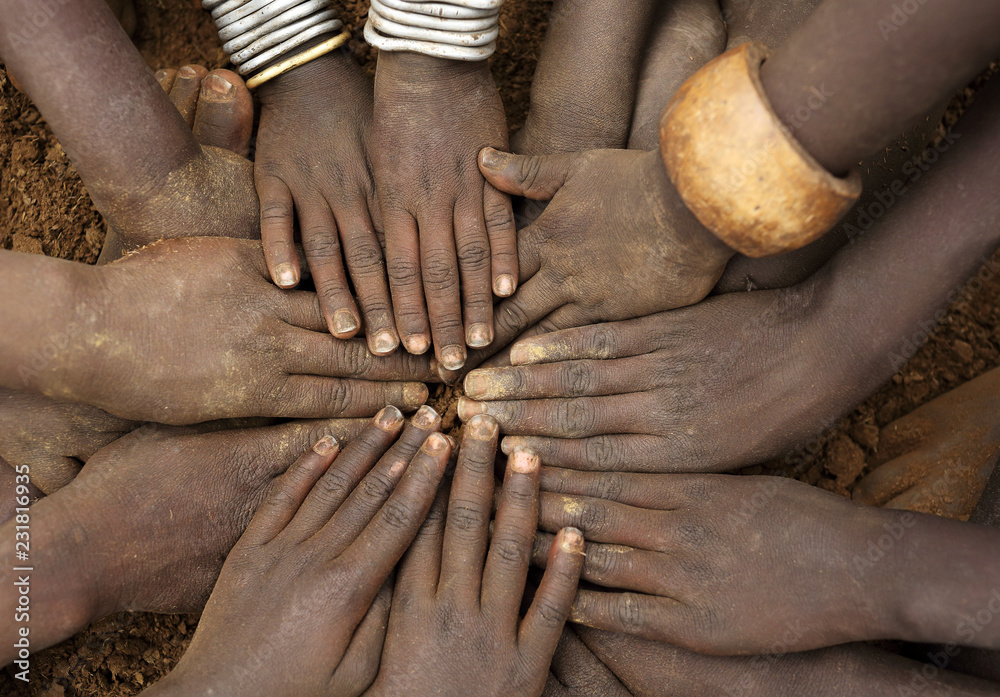 Fototapeta African ceremony of the Mursi tribe, close-up of hands of a group of children, Ethiopia
