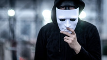 Mystery Hoodie Man With Broken Black Mask Holding White Mask In His Hand. Anonymous Social Masking Or Bipolar Disorder Concept.