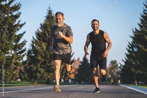 Foto  The father and a son running on the park road