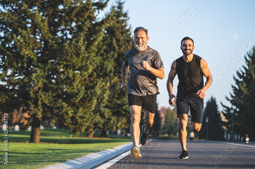 Photo The happy father and a son running on a park road