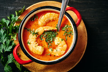Traditional Thai Soup With Shrimp And Coconut Milk In A Red Pot And A Spoon With Parsley