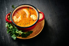Traditional Thai Soup With Shrimp And Coconut Milk In A Red Pot With Parsley
