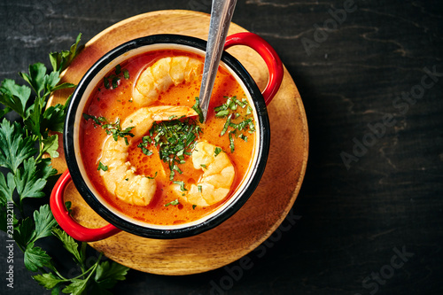 Valokuva traditional Thai soup with shrimp and coconut milk in a red pot and a spoon with