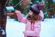 Child Girl Feeding Birds In Winter. Bird Feeder In Snowy Garden, Helping Birds During Cold Season, Teaching Kids To Love And Protect Nature