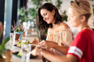 Fototapeta food and people concept - female friends eating at restaurant or cafe