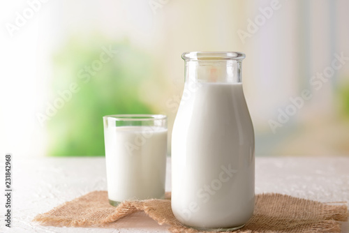 Vászonkép Bottle and glass of tasty milk on light table
