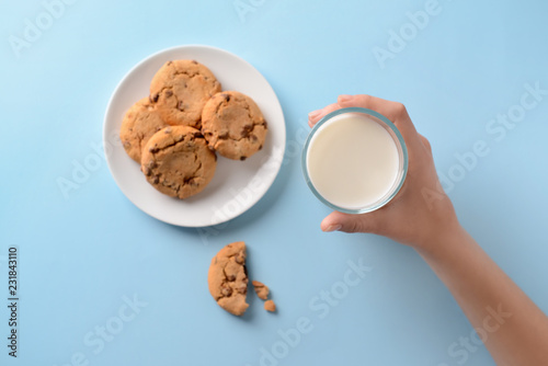 Fotografia Female hand with glass of milk and tasty cookies on color background