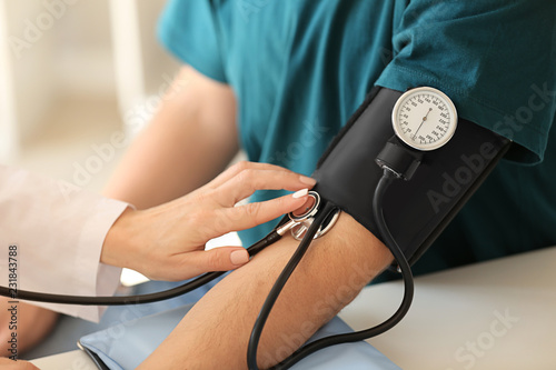 Female doctor measuring blood pressure of male patient in hospital Canvas Print