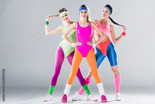 Fototapeta three happy sporty girls standing together and smiling at camera on grey obraz