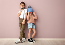 Cute Boy And Girl In Fashionable Clothes Near Color Wall
