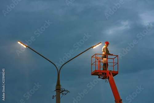 Fotografie, Obraz  Municipal worker with helmet and safety protective equipment installs new diode lights