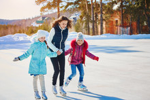 A Group Of Three Girls On A Winter Skating Rink. Roll And Laugh. Skating Rink In Nature.