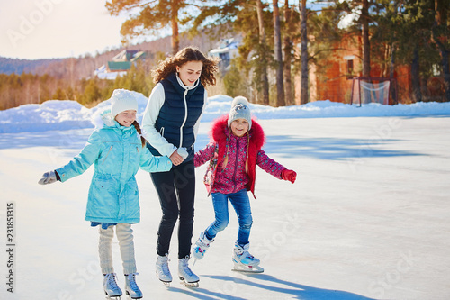 Fotografia A group of three girls on a winter skating rink