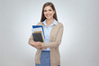 Smiling woman teacher holding books.