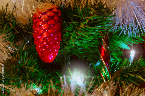 Fotografering  Mysterious Christmas background with vintage Christmas decorations on an artificial fir tree with a luminous garland