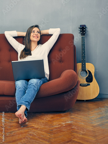 Photo  Casual dressed woman sitting on sofa with laptop.
