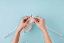Partial View Of Woman With White Yarn And Knitting Needles Knitting On Blue Backdrop