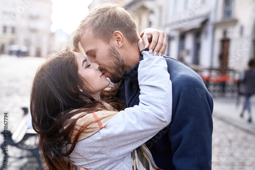 Fotografie, Obraz Portrait of a young romantic enamoured couple hugging and kissing during the city walk
