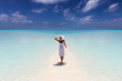 Fernweh Konzept: Elegante Frau in weißem Kleid läuft über einen tropischen Strand mit türkisem Meer und genießt ihren Urlaub