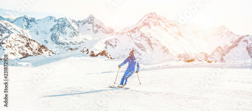 Cuadros en Lienzo Young athlete skiing in alps mountains on sunny day