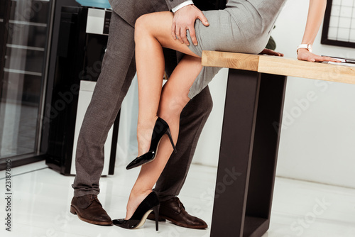 Foto partial view of business colleagues flirting at workplace in office, offirce rom
