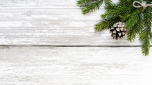 Fir Branch And Pine Cone On White Wood Plank