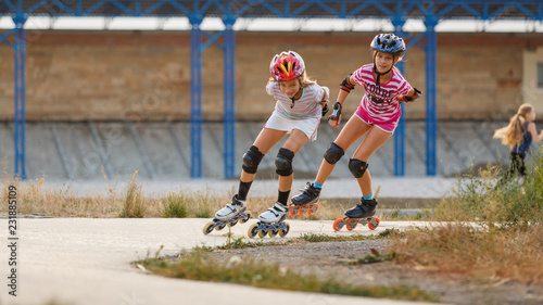 Fotografia Two girls training in speed skating on rollerdrome