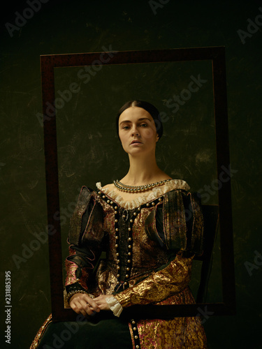 Portrait of a girl wearing a princess or countess dress over dark studio Wallpaper Mural