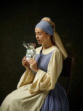 Medieval Woman In Historical Costume Wearing Corset Dress And Bonnet. Beautiful Peasant Girl Wearing Thrush Costume With Sweet Chocolate Bar Over Dark Studio