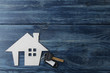 The concept of buying a home. Decorative hut and house keys on a blue wooden background with a place for an inscription. top view