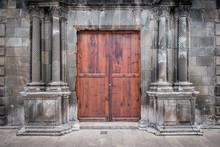 Historic Building Facade With Columns And Wooden Door