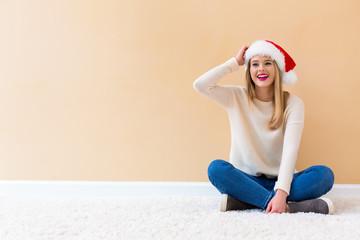 Fototapeta Happy woman with a Santa hat on a white carpet