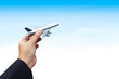 Business hand holding airplane against blue sky and cloud.