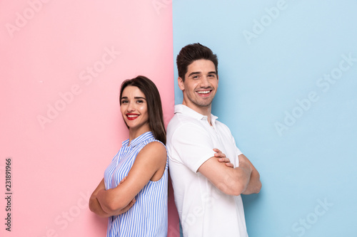 Image of european man and woman in casual wear standing back to back with arms crossed, isolated over colorful background