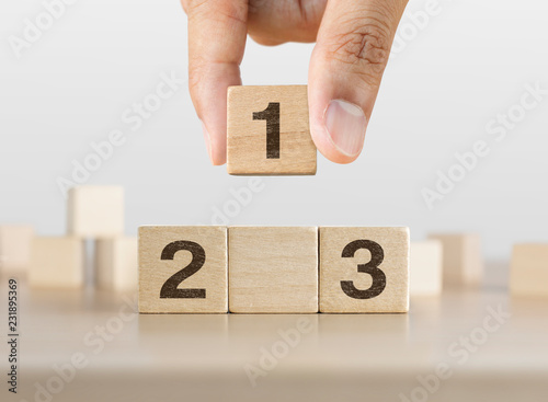Fotografía  Hand arranging wooden blocks stacking as a podium on white background