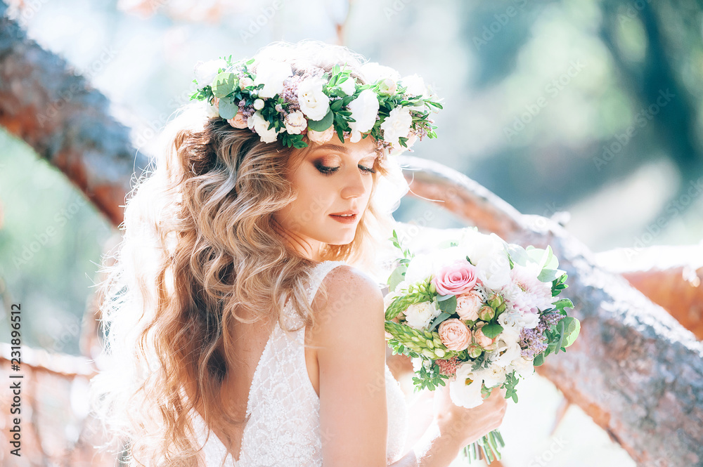 Fototapeta beautiful bride in nature in a coniferous forest in a wreath on her head and a luxurious wedding dress