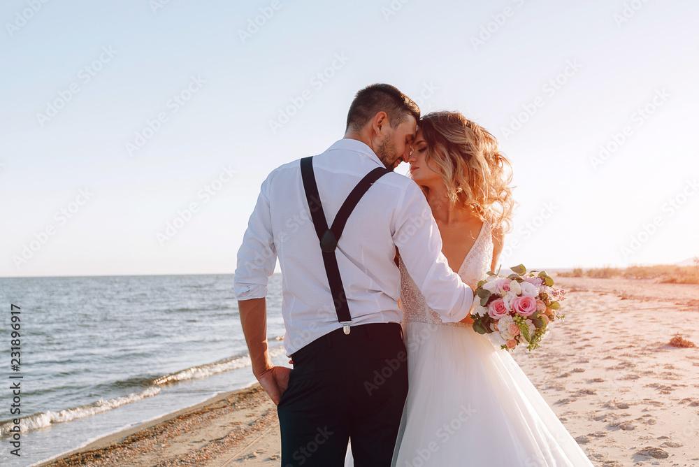 Fototapeta bride and groom on the seashore. wedding concept on the sea, on a fabulous island.