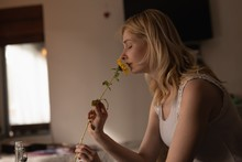 Woman Smelling Flower At Home