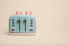 Retro Green 4 Slice Toaster On A Vintage Tan Background With Four Slices Of Toast Popping Out