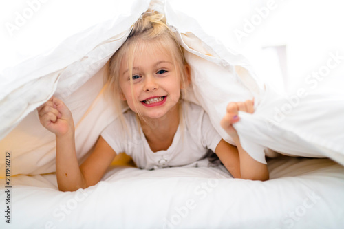 A Cheerful little girl in bed having fun Canvas Print