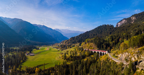 Foto  Panoramic View of a red train crossing the Landwasser Viaduct in the Swiss Alps